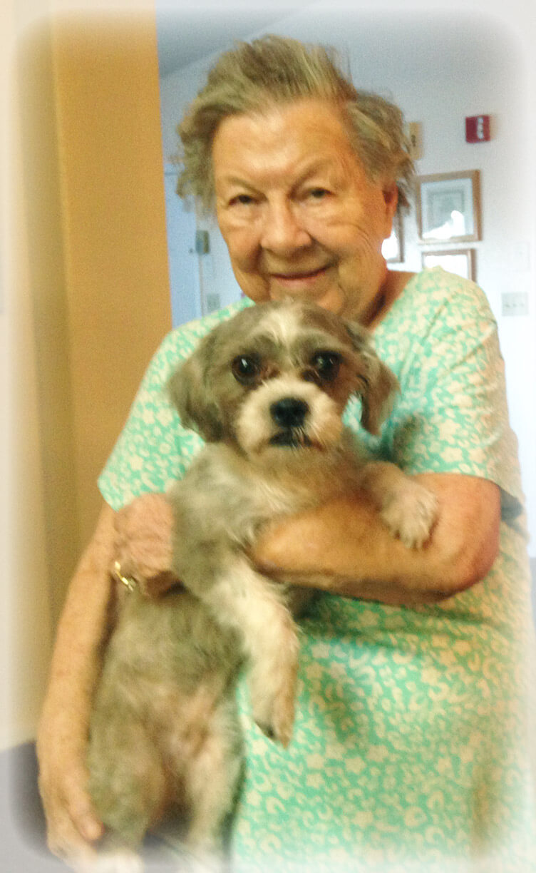 Eden Adult Care Facility resident holding visiting therapy dog